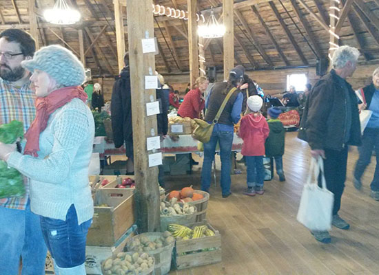 People shopping at The Thanksgiving Farmer's Market at The Round Barn in Vermont
